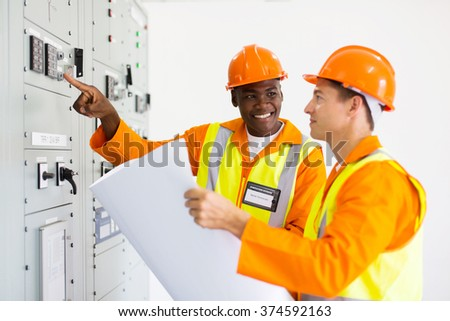 two industrial technicians working in control room - stock photo