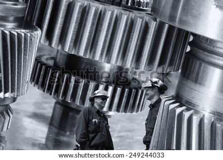 two industry workers and giant cogwheels machinery, engineering and technology - stock photo
