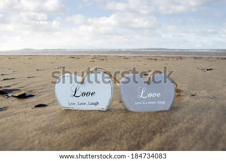 two inscribed wooden love hearts in the sand on a wild Atlantic way Irish beach in summer - stock photo