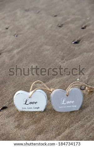 two inscribed wooden love hearts sinking in the quicksand on a wild Atlantic way Irish beach in summer - stock photo
