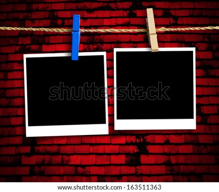 Two instant blank photographs hanging on a clothesline over red brick wall with clipping path  - stock photo