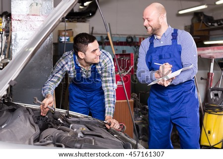 Two insurance agents are measuring loss at car repair shop - stock photo
