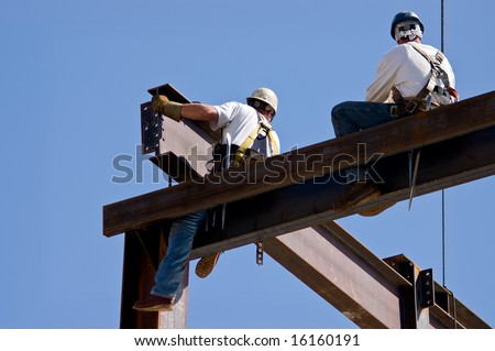 Two ironworkers atop the skeleton of a modern building. One man is positioning a very large beam while the other man watches. - stock photo