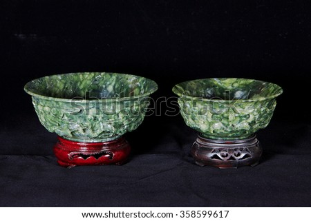 Two Jade bowls with wooden base isolated on dark background. - stock photo