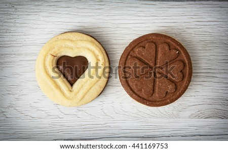 Two jam biscuits in the shape of heart and clover leaf on the wooden background. Food theme. Symbolic sweets. Valentine's Day. - stock photo