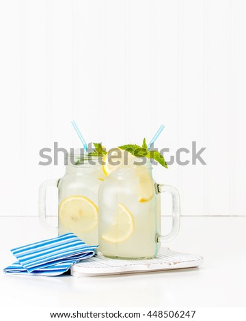 Two jars filled with ice cold homemade lemonade. - stock photo