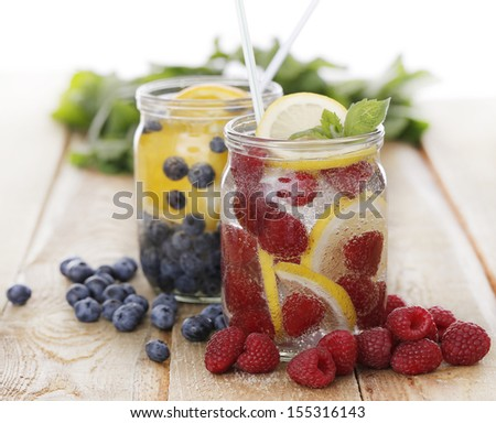Two jars full of different cold drinks on the wooden table - stock photo