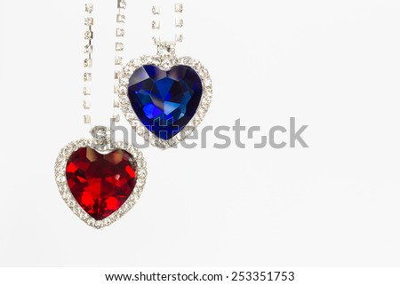 Two jewelry hearts blue and red hanging together isolated on white background - stock photo