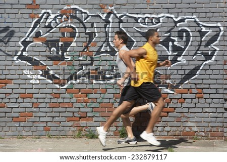 Two Jogger in Front of Wall - stock photo
