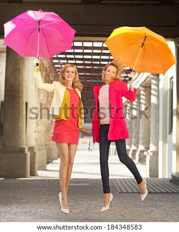 Two joyful girlfriends jumping with umbrellas - stock photo