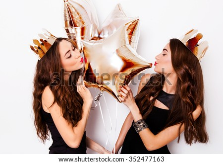 Two joyful pretty friends celebrating new year or birthday party, have fun, drink alcohol , dancing . Emotional faces. Couple sexy elegant women posing indoor studio portrait white background. - stock photo