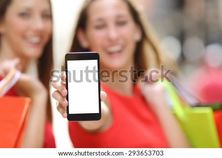 Two joyful shoppers with shopping bags showing a blank smart phone screen in the street - stock photo