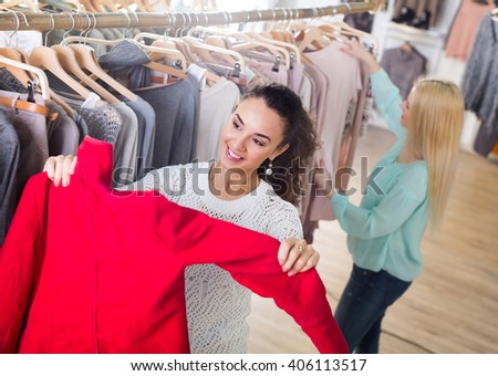 Two joyful smiling young women shopping warm jackets at the apparel store - stock photo