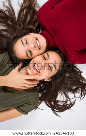 Two joyful teenager girl friends laying on the floor with their heads together - stock photo