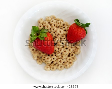 Two juicy strawberries in a bowl of cereal o's. High key, Focus on all subjects. - stock photo