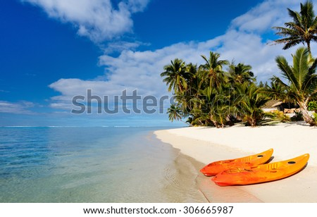 Two kayaks at beautiful tropical beach with palm trees, white sand, turquoise ocean water and blue sky at Cook Islands, South Pacific - stock photo