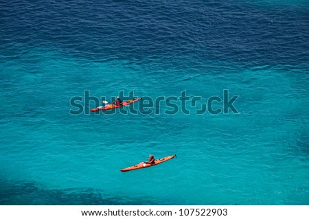 Two kayaks on turquoise sea water near Trebaluger beach, Menorca, Balearic Islands, Spain - stock photo
