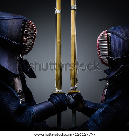 Two kendo fighters opposite each other with bokuto. Japanese martial art of sword fighting - stock photo