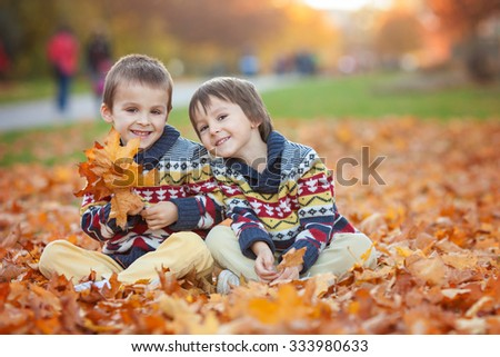 Two kids, boy brothers, playing with leaves in autumn park, sunny afternoon - stock photo