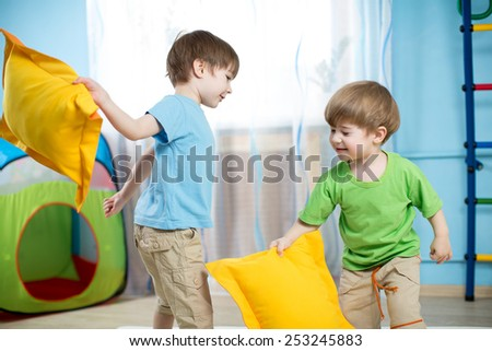 Two kids boys playing with pillows at home - stock photo
