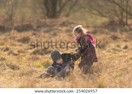 Two kids, brother and sister, playing together on a meadow in early spring and enjoying the first warm sunlight. Extremely small focus range, focus on the children. - stock photo