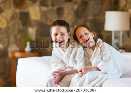 Two kids brother and sister wearing little bathrobes laughing while sitting on bed at hotel room or home - stock photo