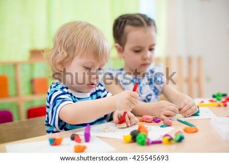 two kids doing arts and crafts in day care centre - stock photo
