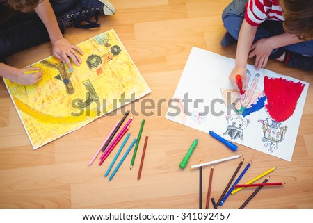 Two kids drawing together on sheets on the floor - stock photo