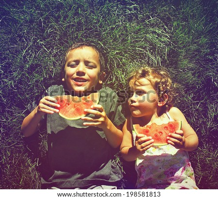 two kids eating watermelon done with a retro vintage instagram filter - stock photo