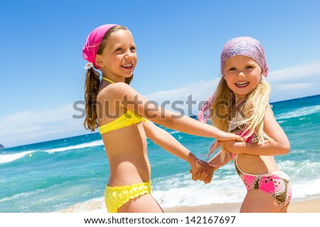 Two kids enjoying a day at the beach together. - stock photo