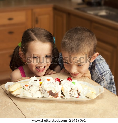 two kids excited over banana split - stock photo