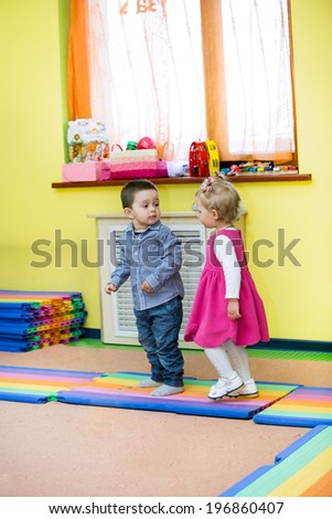 Two kids in Montessori preschool Class. Little girl and boy playing in kindergarten - stock photo
