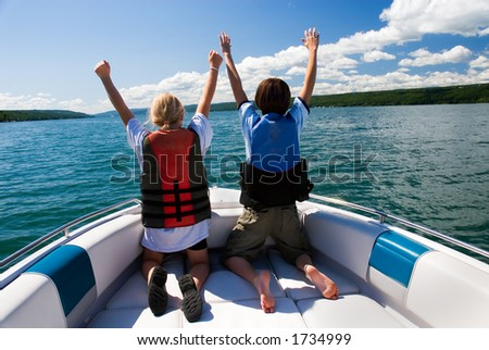 """Two kids in the bow of a motorboat acting out a scene from the movie """"Titanic"""". - stock photo"""