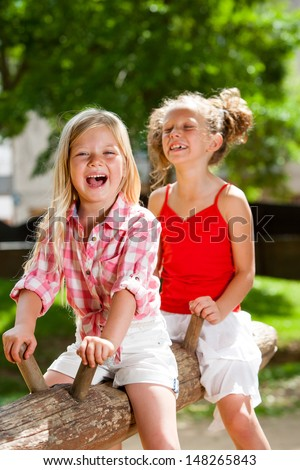 Two kids laughing and swinging on wooden log in park. - stock photo