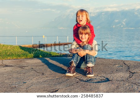 Two kids, little girl and boy resting by the lake on sunset, wearing pullovers and jeans, toned image - stock photo