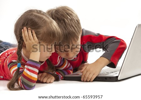 Two kids looking at notebook - laying flat on the floor - stock photo