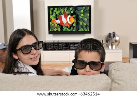 Two kids on couch watching TV with 3d glasses - a series of WATCHING TV images. - stock photo