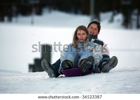 two kids on sled boy and girl - stock photo