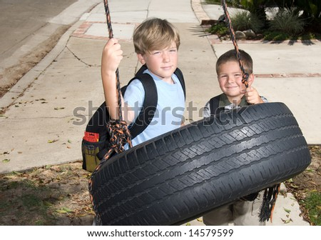 Two kids play on a tire swing after school. - stock photo