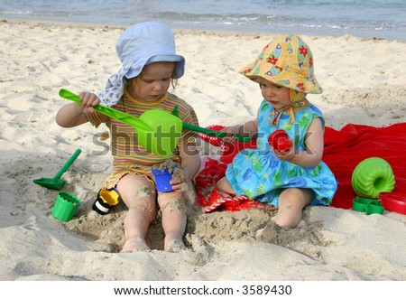 Two kids playing at the beach (one year and three years old) - stock photo