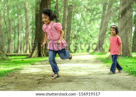 Two kids playing at the park (blurry on main character because of movement and motion jumping) - stock photo