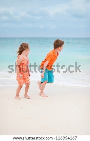Two kids playing at tropical beach - stock photo