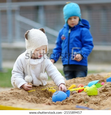 Two kids playing in a sandbox on autumn day - stock photo