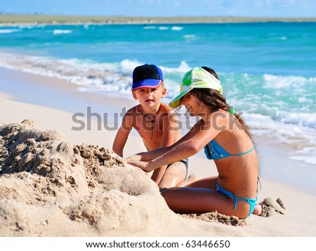 Two kids playing in sand at the beach - stock photo