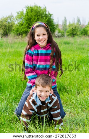 Two kids playing on green grass, outdoor shoot - stock photo