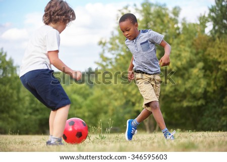 Two kids playing soccer in summer - stock photo