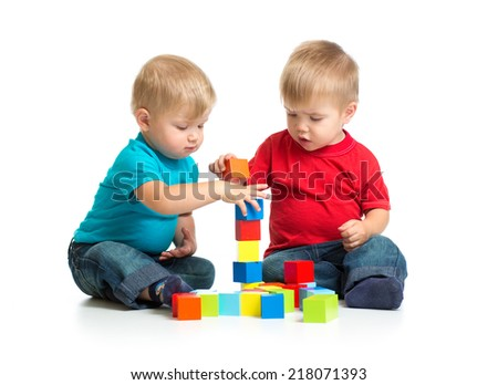 Two kids playing wooden blocks together building tower - stock photo
