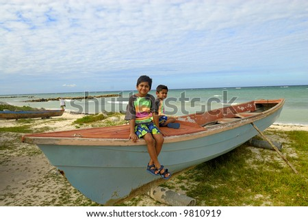 two kids relaxing on top of a fishing boat - stock photo