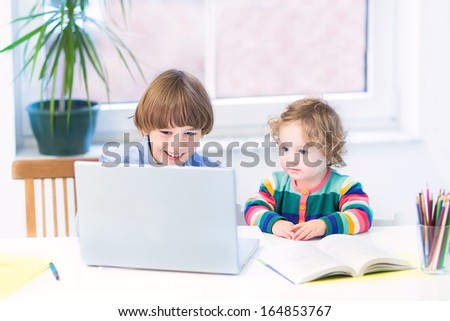 Two kids, school boy and his toddler sister, playing together with a laptop sitting at a white desk at a window - stock photo