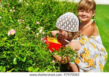 Two kids watering flowers in garden - stock photo